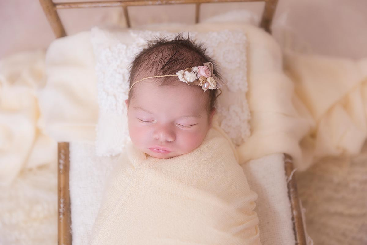Newborn girl in a tiny bed