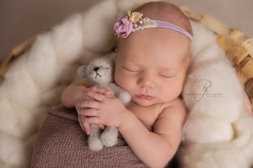 Baby snuggling teddy